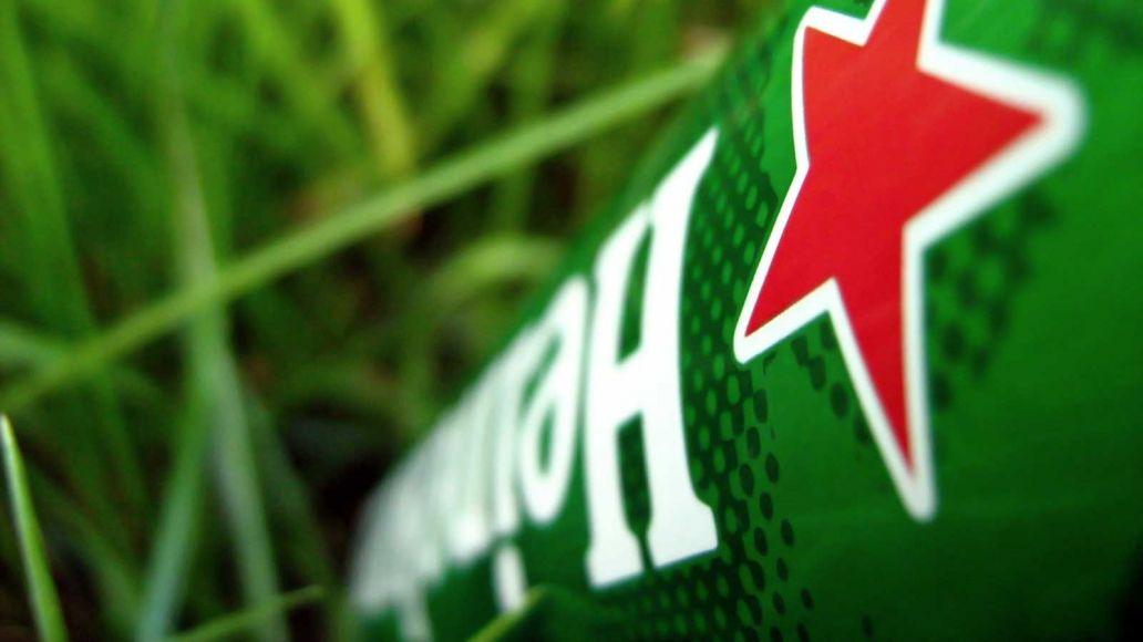 close up van een groen heineken flesje in gras